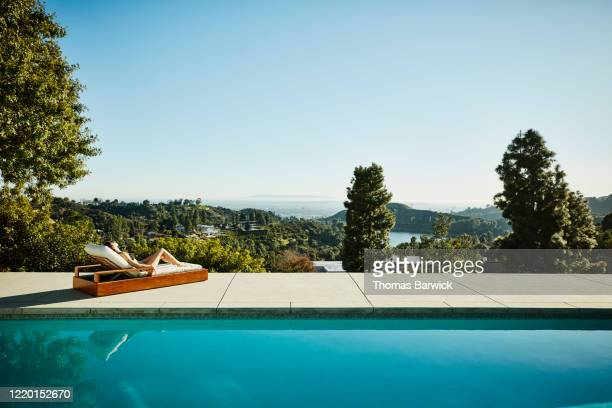 woman relaxing in lounge chair at edge of pool - lying down stock pictures, royalty-free photos & images