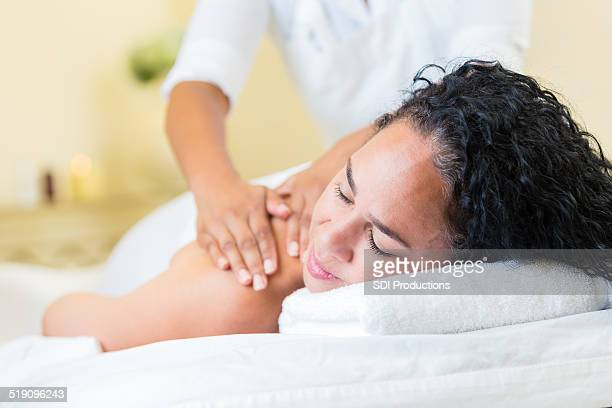 woman relaxing in luxurious spa during massage treatment - massage black woman stock photos and pictures