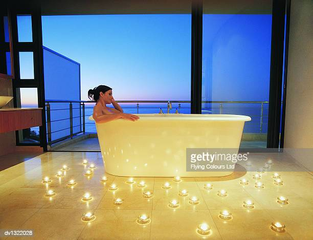 Woman Relaxing in Luxury Bath Surrounded By Candles Against Open View of the Sea