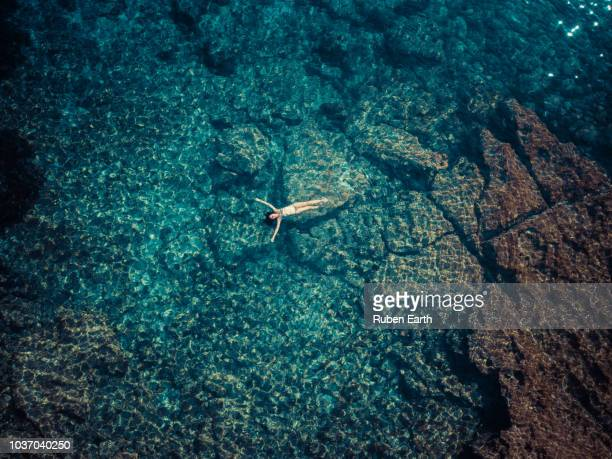 woman relaxing in mediterranean sea aerial - insel ibiza stock-fotos und bilder
