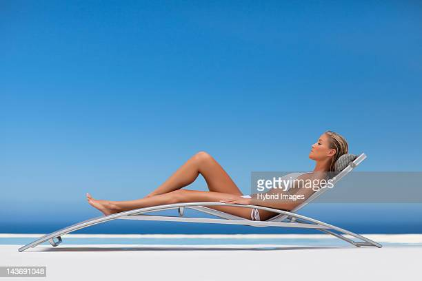 Woman relaxing in modern chair by pool