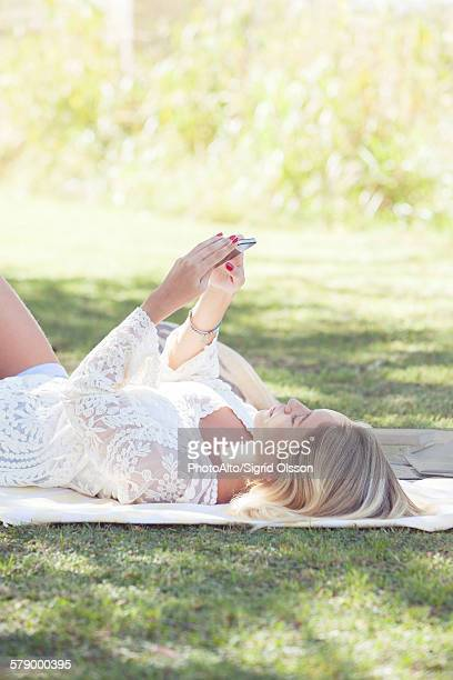 Woman relaxing in park with smartphone