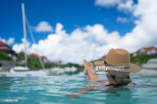 woman relaxing in pool at tropical marina - marina stock pictures, royalty-free photos & images