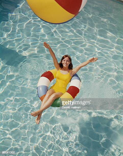 Woman relaxing in pool float tossing beach ball