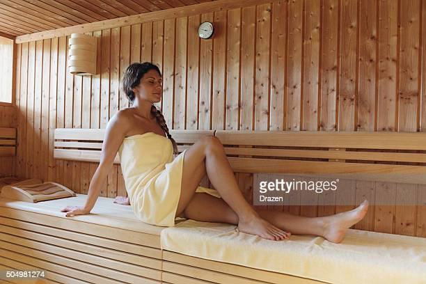 Woman relaxing in sauna and enjoys healthy lifestyle