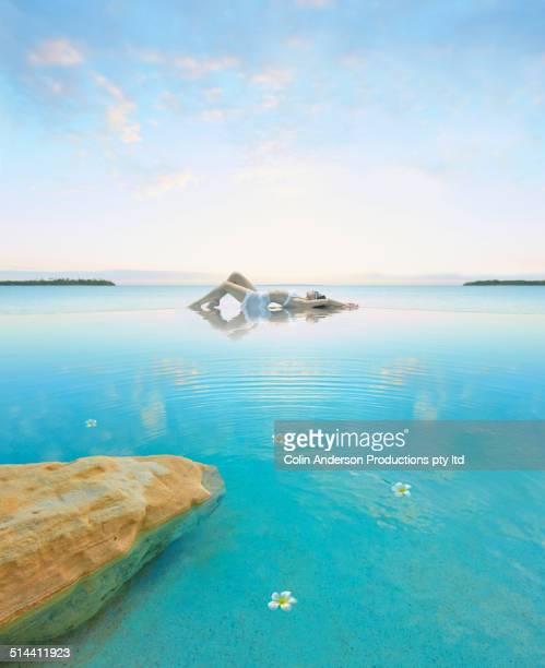 Woman relaxing in still pool overlooking ocean