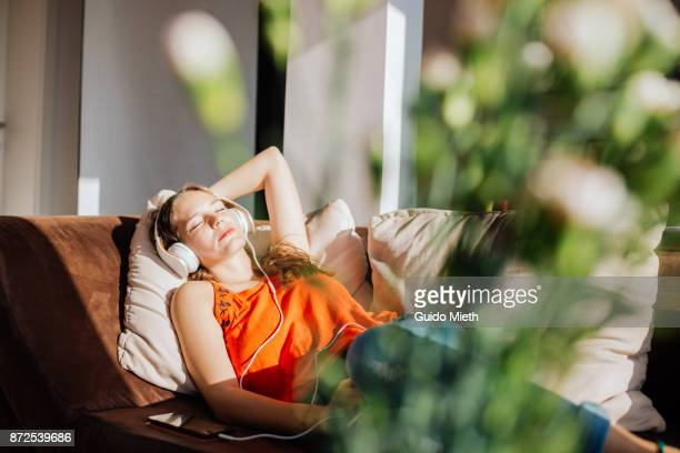 woman relaxing in sunlight. - zuhören stock-fotos und bilder