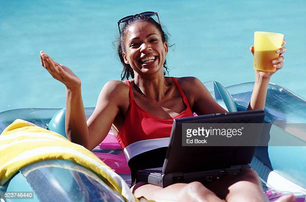 Woman Relaxing in Swimming Pool with Laptop