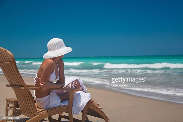 woman relaxing in teak chair on the beach in Florida