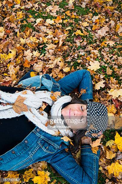 """woman relaxing in the fallen autumn leaves. - """"martine doucet"""" or martinedoucet stock pictures, royalty-free photos & images"""