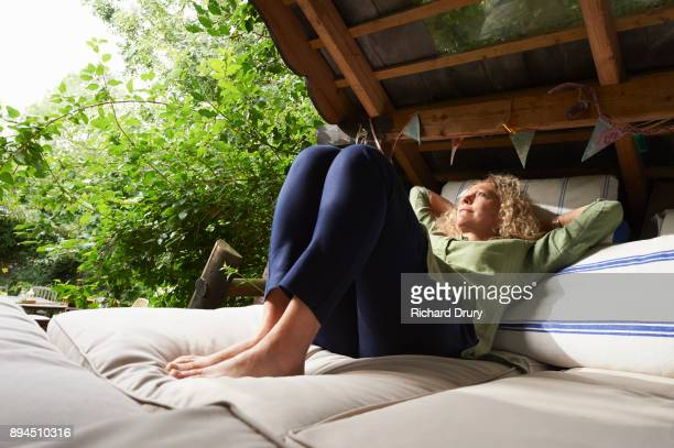 Woman relaxing in treehouse