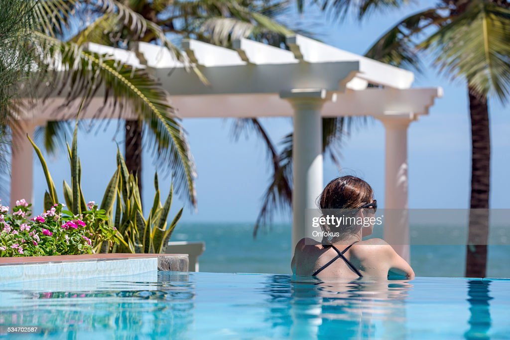 Woman Relaxing Inside Infinity Pool At Tropical Resort : Stock Photo