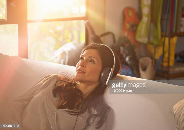 A woman relaxing listening to music on headphones.