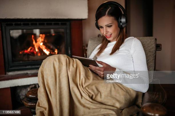 woman relaxing near fireplace - warming up stock pictures, royalty-free photos & images