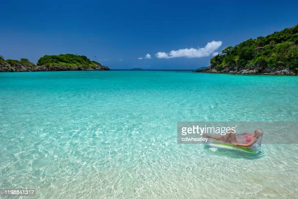 woman relaxing on a raft at a caribbean beach - inflatable raft stock pictures, royalty-free photos & images