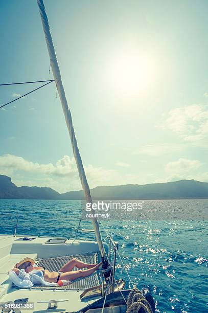 Woman relaxing on a sailboat.