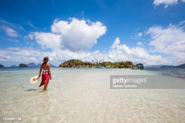 woman relaxing on a sandbar near island - philippines stock pictures, royalty-free photos & images