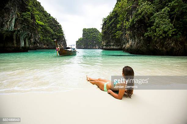 A woman relaxing on a secluded beach.