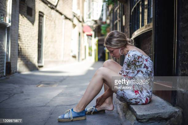 woman relaxing on a stone bench in london - swollen ankles stock pictures, royalty-free photos & images