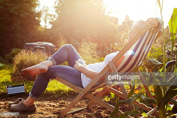woman relaxing on allotment - gemüsegarten stock-fotos und bilder