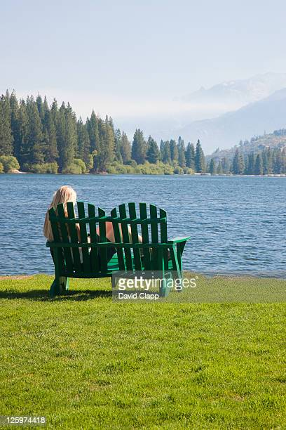 Woman relaxing on an adirondack chair on the waters edge at Hume Lake, Hume Lake Christian Camp, Fresno County, Sequoia National Park, East Central California, Sierra Nevada, California, United States of America