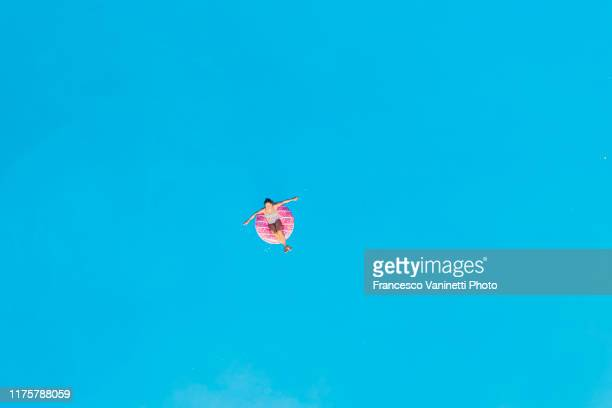 woman relaxing on an inflatable ring on the sea, lefkada, greece. - floating on water stock pictures, royalty-free photos & images