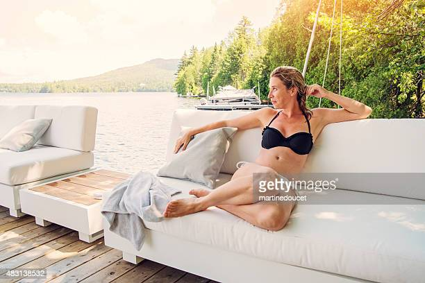 Woman relaxing on an outdoor couch on a lake pier.