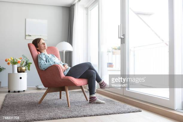 woman relaxing on armchair at home - relaxation stock pictures, royalty-free photos & images