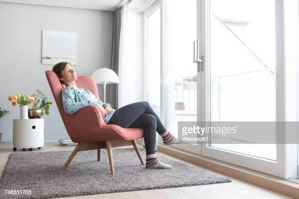 woman relaxing on armchair at home - armstoel stockfoto's en -beelden