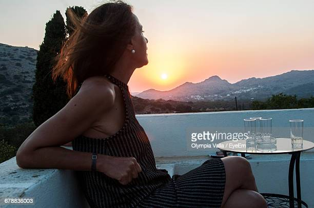 Woman Relaxing On Balcony At Sunset