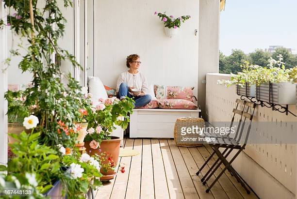 woman relaxing on balcony - balcony stock pictures, royalty-free photos & images