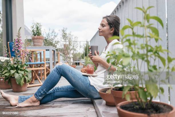 woman relaxing on balcony - escapism stock photos and pictures