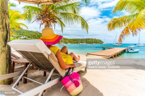 woman relaxing on beach bed, caribbean, antilles - vacances à la mer photos et images de collection