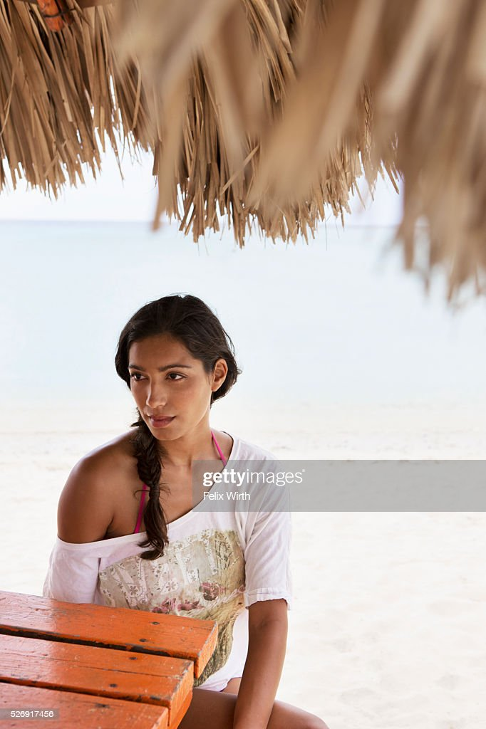 Woman relaxing on beach under sunshade : Stock Photo