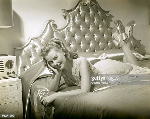 Woman relaxing on bed in night gown