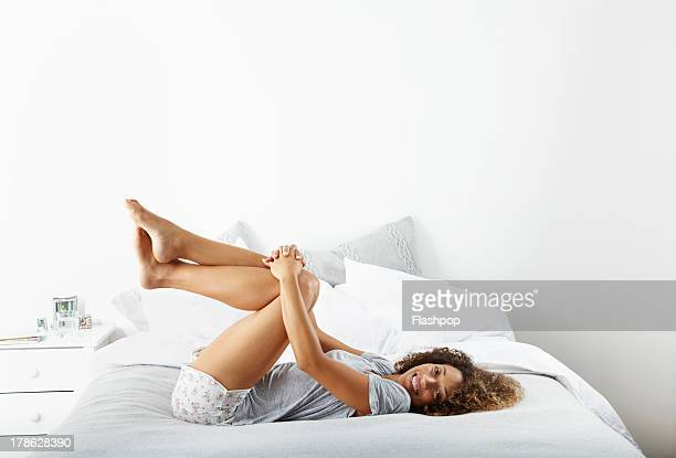 woman relaxing on bed - women in slips stock pictures, royalty-free photos & images