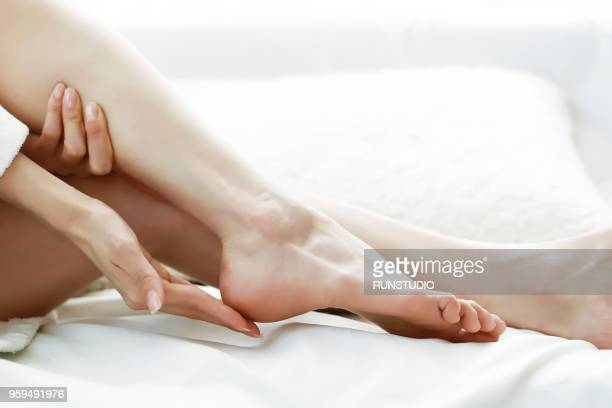 woman relaxing on bed, touching bare legs - beautiful bare women photos et images de collection