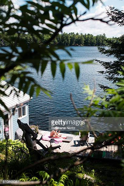 woman relaxing on cottage dock - ontario canada stock pictures, royalty-free photos & images