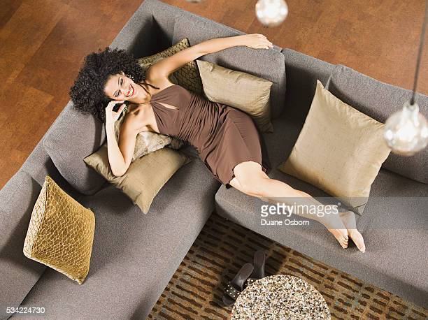 woman relaxing on couch - cocktail dress stock pictures, royalty-free photos & images