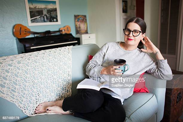 Woman relaxing on couch with coffee and a book