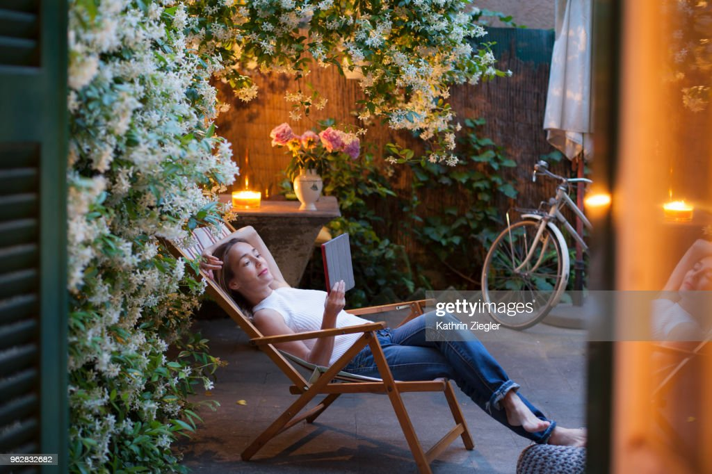 Woman relaxing on deck chair in backyard at dusk, reading on digital tablet : Photo