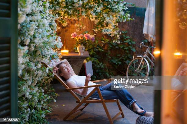 woman relaxing on deck chair in backyard at dusk, reading on digital tablet - relaxation stock pictures, royalty-free photos & images