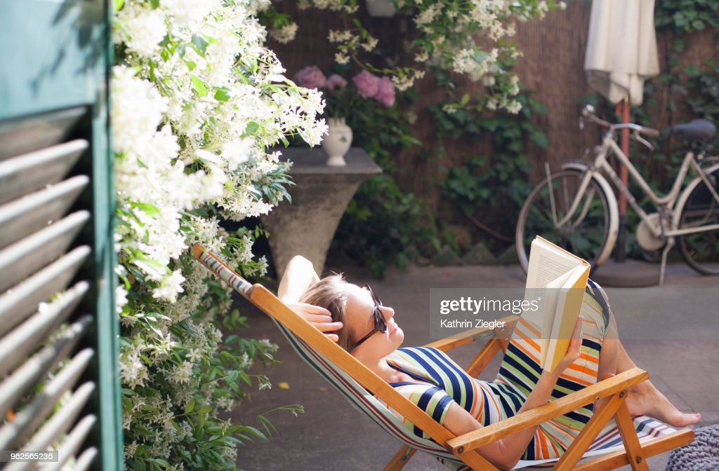 Woman relaxing on deck chair in backyard, reading a book : Stockfoto