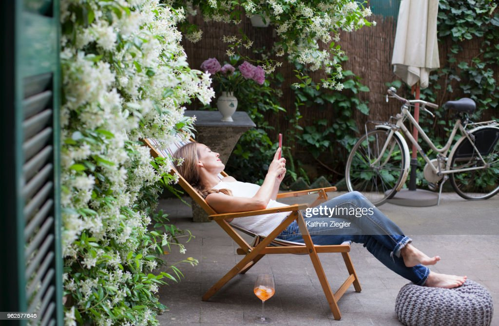 Woman relaxing on deck chair in backyard, reading on digital tablet : Stock Photo