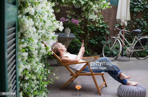 woman relaxing on deck chair in backyard, reading on digital tablet - deck chair stock pictures, royalty-free photos & images