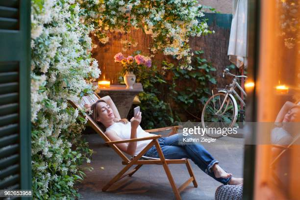 woman relaxing on deck chair in backyard, reading on mobile phone - pergola photos et images de collection
