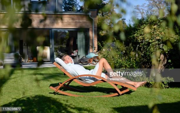 woman relaxing on deck chair in her garden - transat photos et images de collection