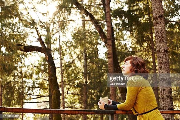 Mujer relajante en la terraza en la naturaleza