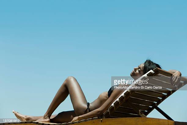 Woman relaxing on deckchair in sun