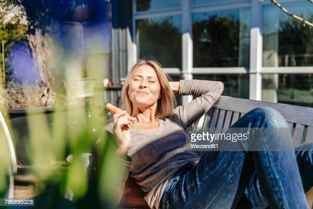 Woman relaxing on garden bench eating a carrot